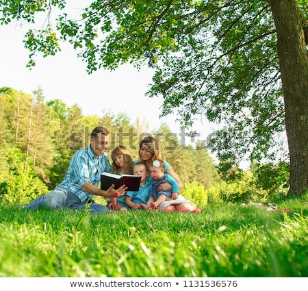 young family reading the bible in nature stock photo © koca777