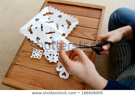 Woman making paper snowflakes at a wooden craft table Stock photo © sarahdoow