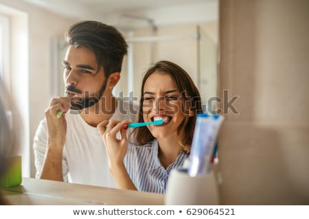 young couple brushing teeth in bathroom stock photo © monkey_business