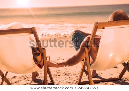 cute couple holding hands while lying on their deck chairs stock photo © wavebreak_media