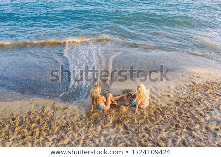 woman reclining in swimsuit on beach at sunset stock photo © iofoto