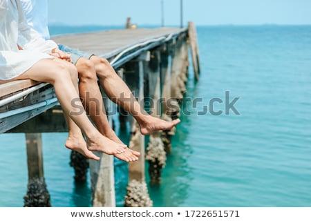 Legs hanging of a Jetty Stock photo © Klinker