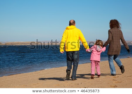 Family of three people walking along beach. View from back. Stock photo © Paha_L