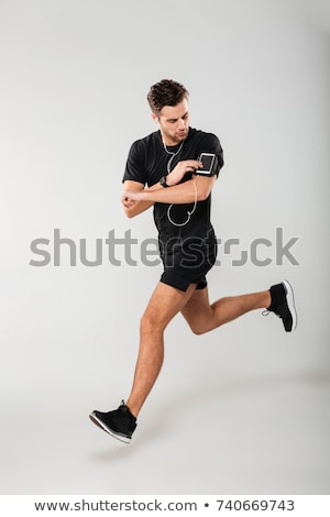 Stock photo: Man jogging with earphones and smartphone.