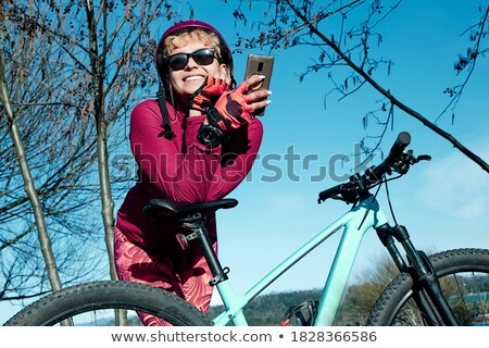 Happy woman in cycling helmet on bicycle using smartphone Stock photo © deandrobot