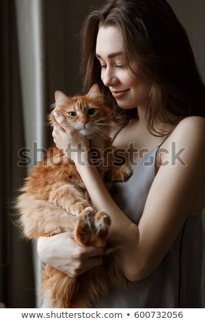 Vertical image of pleased woman in nightie holding cat Stock photo © deandrobot