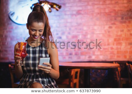 Woman having cocktail while using mobile phone stock photo © wavebreak_media