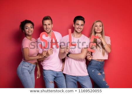 Stock photo: Group of smiling young people posing with sale letters.