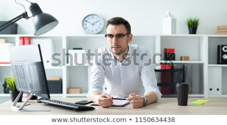 a young man in glasses stands near a table in the office and holds a pencil in his hands stock photo © traimak