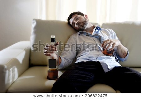 drunk man with glass of alcohol sleeping at home stock photo © dolgachov