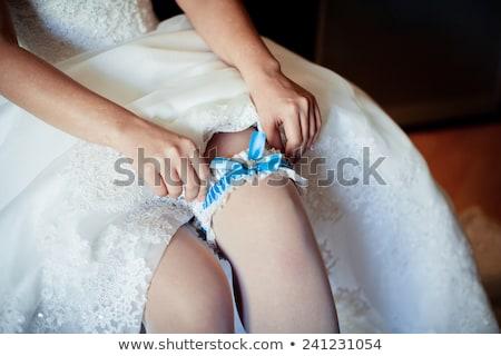 Bride putting on wedding garter Stock photo © ruslanshramko