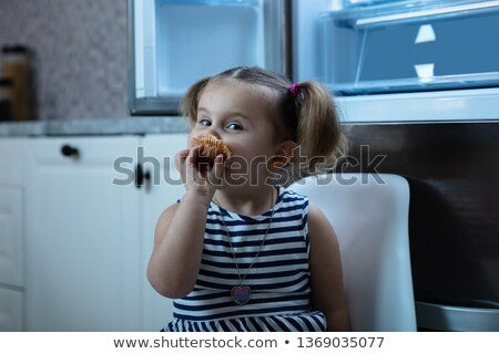 Girl Eating Cupcake Sitting In Front Of Open Refrigerator Stock photo © AndreyPopov