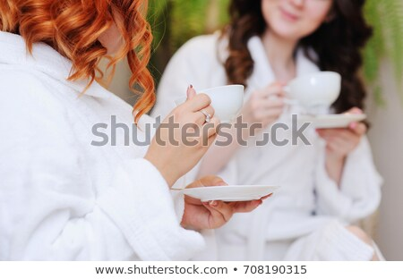 Two women in white robes drinking tea after spa treatments  Stock photo © dashapetrenko