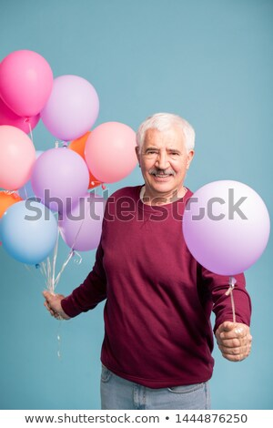 Cheerful mature man giving you one balloon from bunch Stock photo © pressmaster