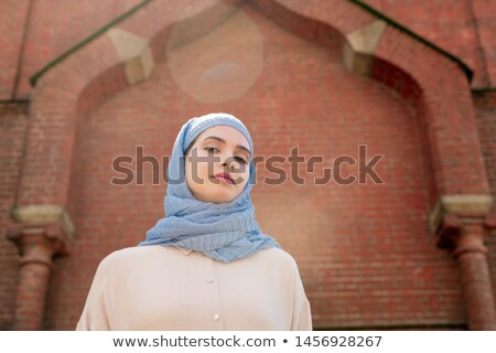 Young muslim woman in hijab standing by wall of oriental palace Stock photo © pressmaster