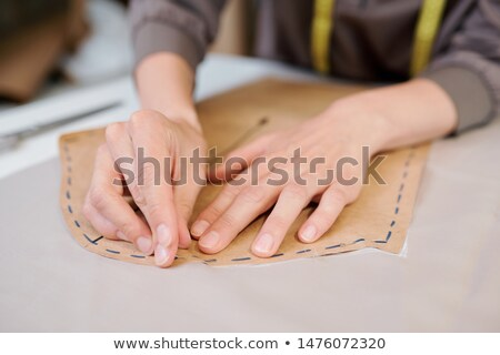 Young female tailor pinning paper workpiece to piece of fabric Stock photo © pressmaster
