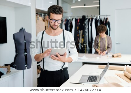 Young serious male tailor with tablet looking through online creative ideas Stock photo © pressmaster
