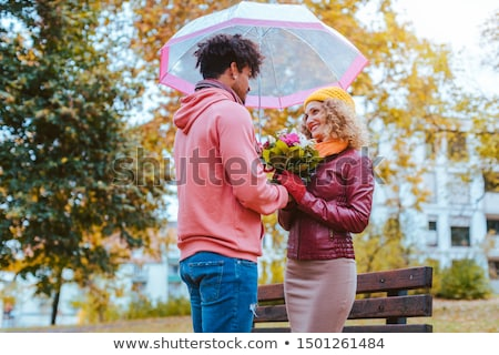Black man giving flowers to his Caucasian girlfriend in fall Stock photo © Kzenon