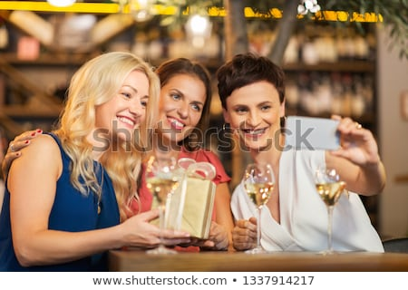 Stock photo: women with gift taking selfie at wine bar
