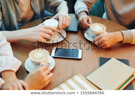 Hands of college friends sitting by wooden table in cafe and having cappuccino Stock photo © pressmaster