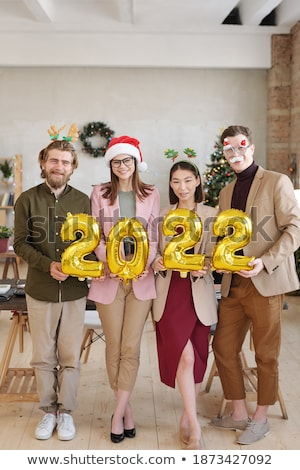 Two happy businesswomen with inflatable numbers standing in front of colleague Stock photo © pressmaster