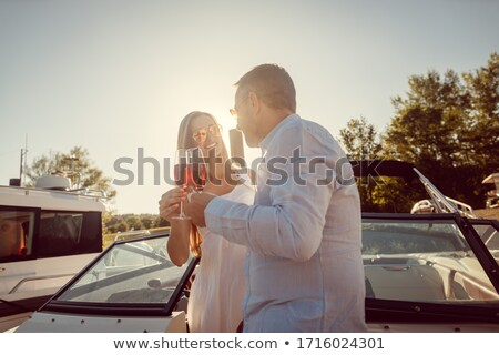 Couple in a river boat or yacht toasting with sparkling wine Stock photo © Kzenon