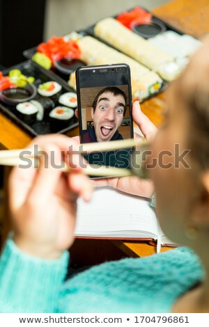 Woman eating sushi while talking on the phone Stock photo © photography33