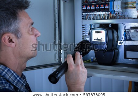 Electrician examining a fusebox with a torch Stock photo © photography33