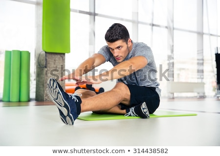portrait of a handsome man stretching at gym stock photo © deandrobot