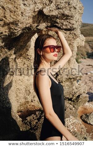 Beautiful woman in black bikini standing near cliff on beach. Outdoor shot. Stock photo © svetography