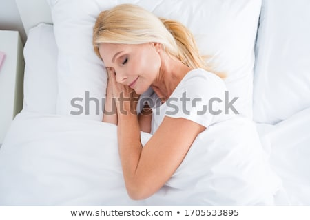Stock photo: young pretty blond woman in bed covered white sheets smiling che