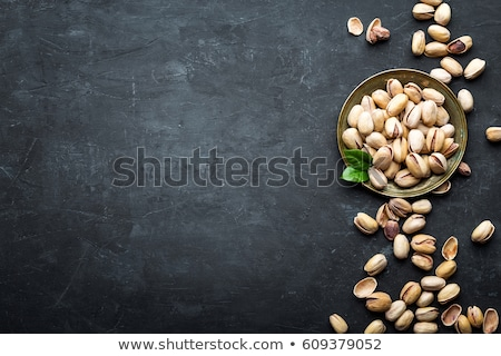 Pistachios nuts on dark background, top view, healthy snack Stock photo © yelenayemchuk