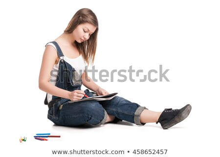 young woman happily sitting on the floor drawing in her note pad back view stock photo © julenochek