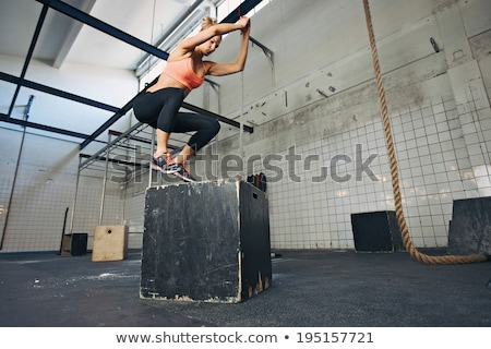 Female athlete is performing box jumps at gym Stock photo © vlad_star