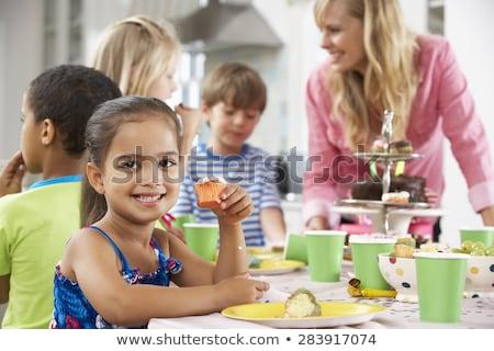 Girls having a tea party in field Stock photo © IS2