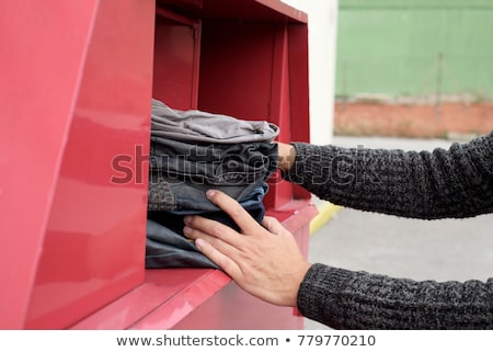man depositing used clothes in a clothing bin Stock photo © nito
