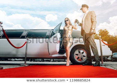 Driver helping VIP woman or star out of limo on red carpet Stock photo © Kzenon