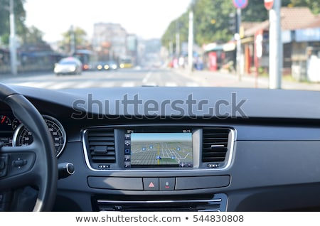 View from inside a car on a part of dashboard with a navigation unit and blurred street in front of  Stock photo © sarymsakov