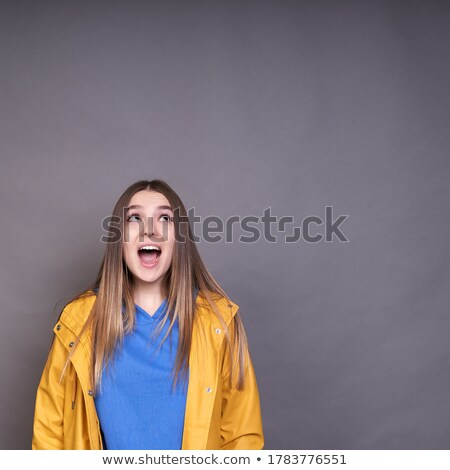 Image of joyful woman 20s wearing yellow raincoat looking at cam Stock photo © deandrobot
