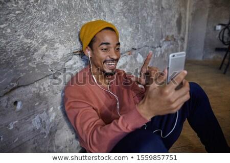 Szczęśliwy facet ciemne włosy posiedzenia piętrze Zdjęcia stock © deandrobot
