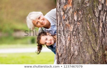 Grootmoeder kleindochter achter boom park familie Stockfoto © dolgachov