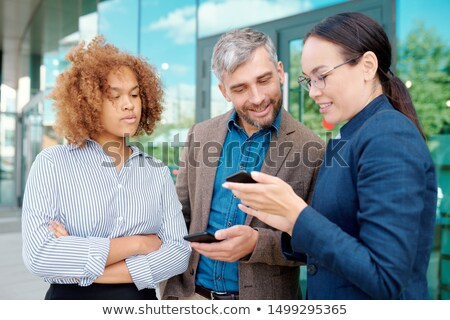 Two young employees with smartphones looking through message history Stock photo © pressmaster
