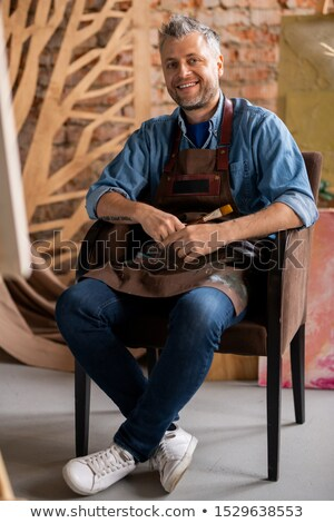 Happy professional artist in workwear looking at you with toothy smile Stock photo © pressmaster