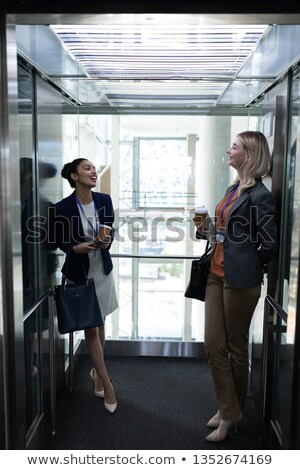 front view of happy young multi ethnic businesswomen coffee cup interacting with each other in moder stock photo © wavebreak_media