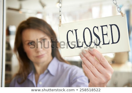 Business store owner turning closed sign at shop doorway Stock photo © boggy