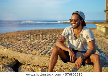 Portrait of attractive and happy man on the beach relaxing and d Stock photo © HASLOO