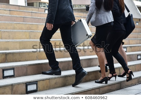 business man holding brief case and walking Stock photo © feedough