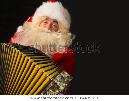 Santa Claus sitting in armchair at home and playing music on acc Stock photo © HASLOO