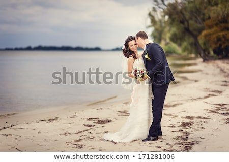 Foto d'archivio: Bouquet And Newly Married Couple Kissing
