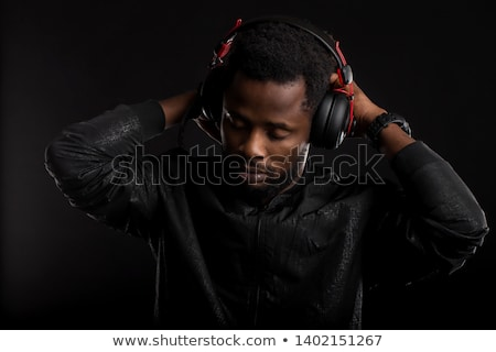 Male DJ listening to music on headphones with eyes closed Stock photo © stevanovicigor